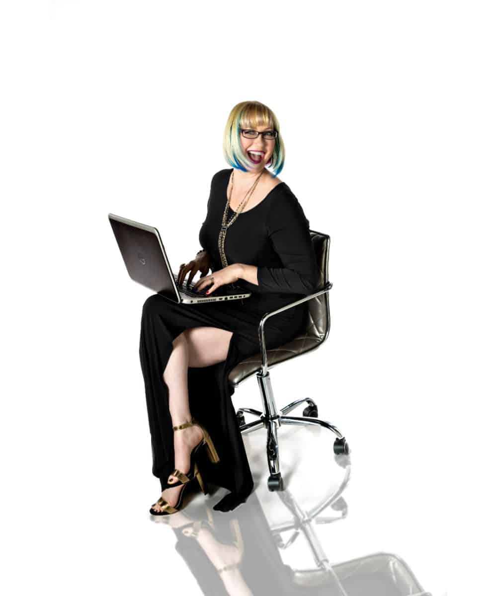 Dorci sitting with computer in black dress having fun